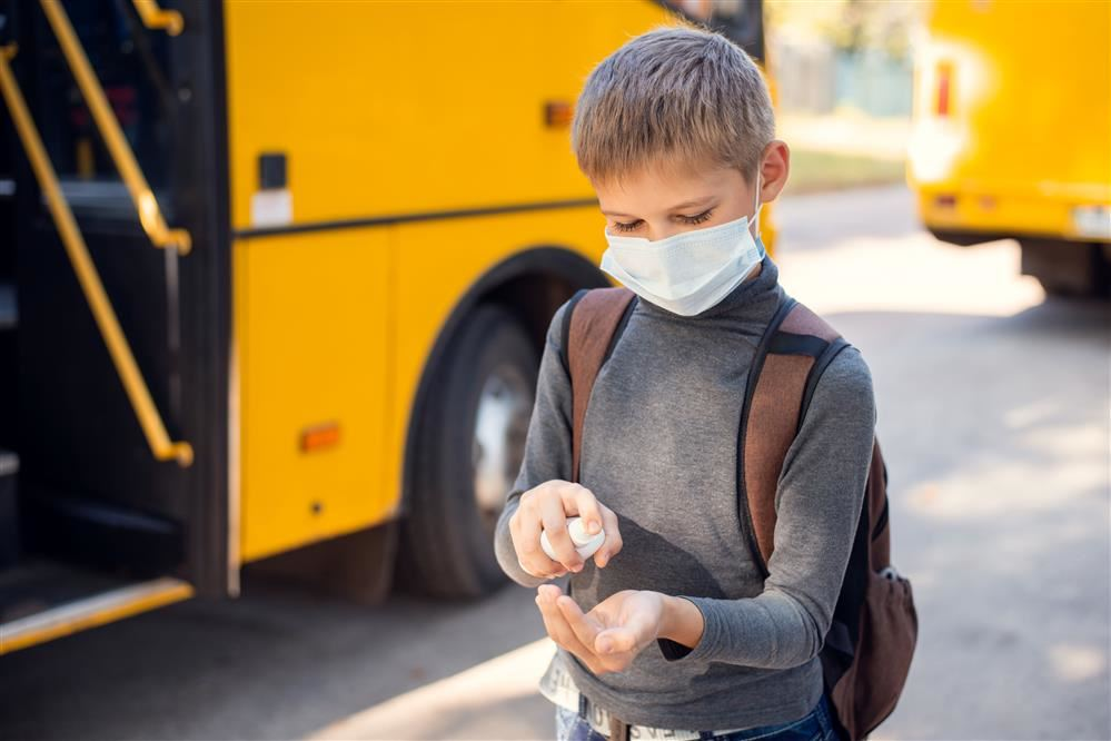 student with mask at school bus