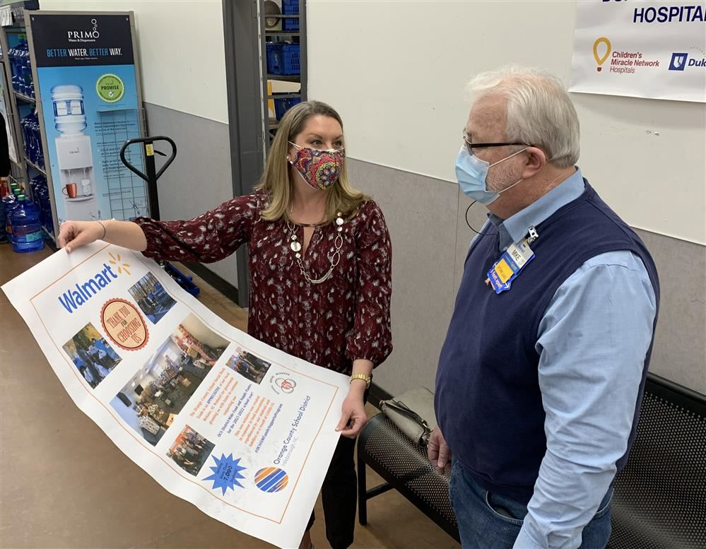 Callie McBroom presents a poster to the Store Lead, to show appreciation to Walmart of Mebane